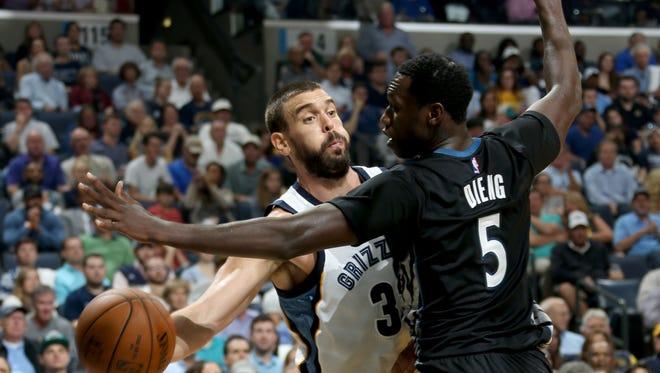 Memphis Grizzlies Marc Gasol passes around the defense of Minnesota Timberwolves Gorgui Dieng.