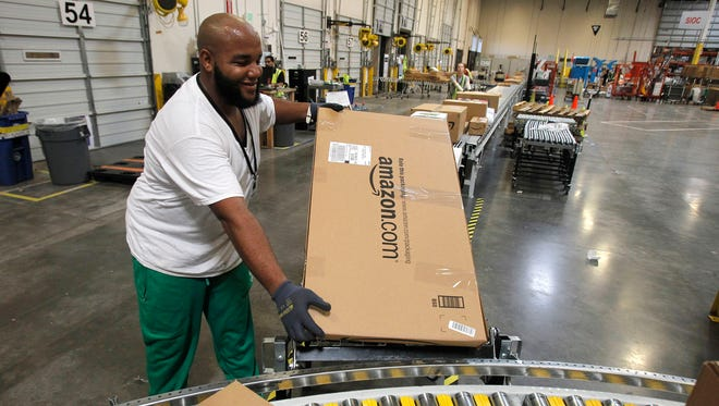 Leacroft Green sorts packages at an Amazon.com fulfillment center in Goodyear, Ariz.