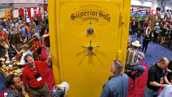 NRA members looks at a large gun safe that was on display at the NRA convention's exhibit hall on Saturday April 11, 2015.