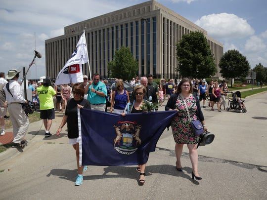 Elizabeth Peterson, Patricia Ceresa and Shelley Newman lead a group of hundreds marching in memory of bailiffs Ron Kienzle and Joseph Zangaro from the Berrien County Courthouse.