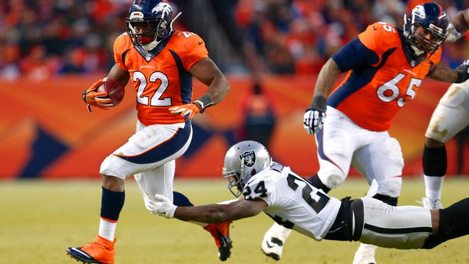 Denver Broncos running back C.J. Anderson (22) runs past the tackle of Oakland Raiders free safety Charles Woodson (24) in the fourth quarter Sunday at Sports Authority Field at Mile High. The Broncos defeated the Raiders 47-14.