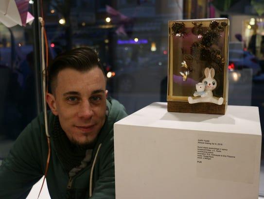 Justin Ayala with his artwork displayed at Creative