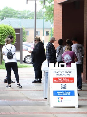 People needing to file for unemployment benefits stand in line on Friday, April 24, 2020, outside the state office in downtown Fort Smith. Sebastian County on Tuesday had a 7.1% unemployment rate.