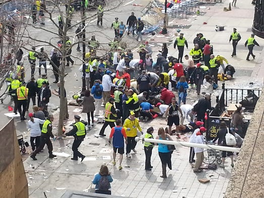 Runners and people from the crowd lie wounded on the ground in the midst of chaos after a bombing at the 2013 Boston Marathon.