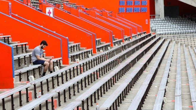A man looks at his phone while sitting alone in Ben Hill Griffin Stadium on the University of Florida campus in April.