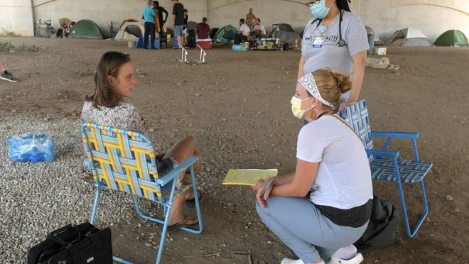 """A pair of lawn chairs become an impromptu doctor's office beneath a bridge in downtown Peoria as Dr. Mary Stapel and Dr. Vivian Wrenn meet with Tamera """"Mississippi"""" Bishop on a recent Thursday morning."""