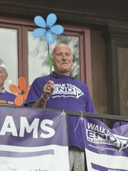 Greg Lothrop, who is living with vascular dementia, holds a blue flower to represent those living with Alzheimer's disease or a related dementia during the opening ceremony for the Walk to End Alzheimer's at the Shelburne Museum on Sunday, Sept. 18, 2016.