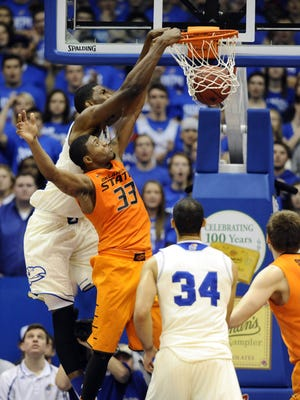 Kansas center Joel Embiid complete the alley-oop with a slam over Oklahoma State guard Marcus Smart.