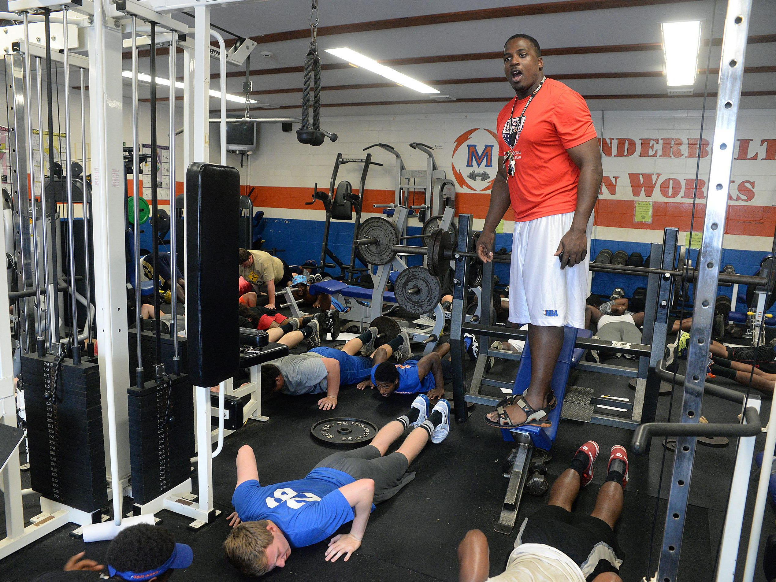 Millville football coach Dennis Thomas leads a strength and power training session in the school's weight room.