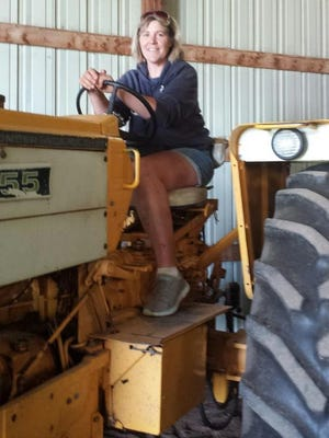 Driving tractor is Johnson's favorite job on the farm, because she gets to smell the fresh air and enjoy the beautiful scenery of the countryside.