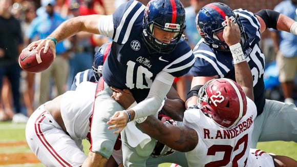 Mississippi quarterback Chad Kelly (10) breaks away from an attempted tackle by Alabama linebacker Ryan Anderson (22) in the first half of an NCAA college football game, Saturday, Sept. 17, 2016 in Oxford, Miss. (AP Photo/Rogelio V. Solis)