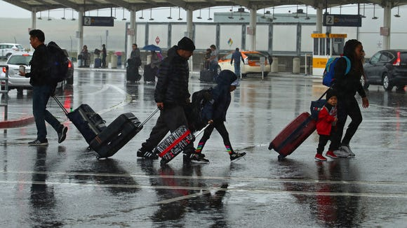 Travelers walk during a rainstorm to the terminals