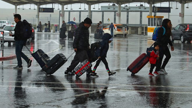 Travelers walk during a rainstorm to the terminals at Oakland International Airport on April 6, 2018, in Oakland, Calif.