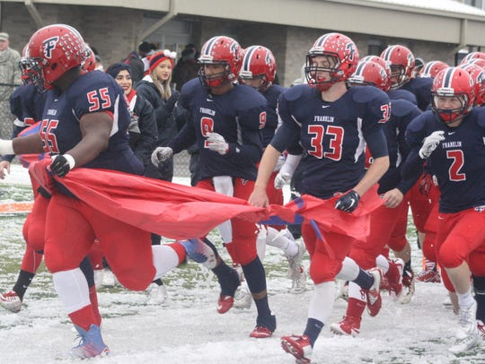 Franklin players charge through a banner in the moments