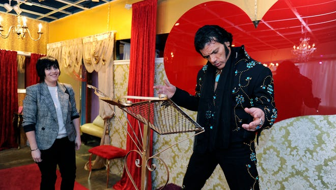 """Honky Tonk"" Elvis impersonator Wes Bowling practices his moves at the Rhinestone Wedding Chapel at the Arcade in downtown Nashville as wedding chapel photographer Kendra Kantz looks on."
