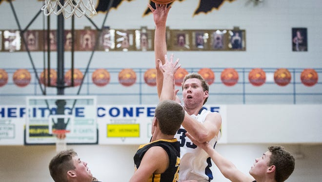 Delta's Adam Haynes fights for a shot past Cowan's defense during their game at Delta High School Friday, Dec. 2, 2016.