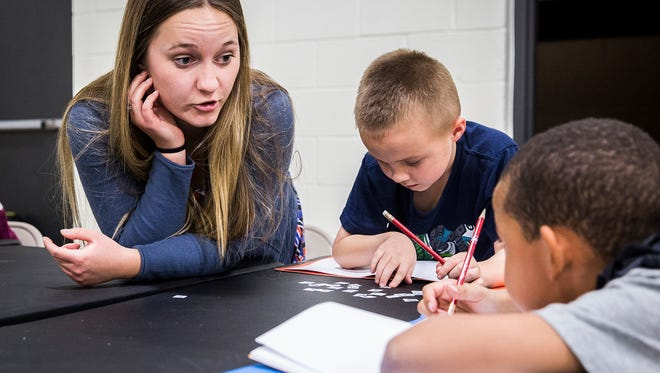 Ball State teaching majors guide children through a science lesson after school at the Buley Center on Tuesday afternoon. In addition to educational programs and structured play, the Buley Center offers dinner to its more than 70 daily attendees.