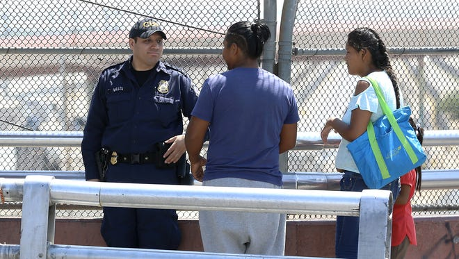 A Customs and Border Protection officer talks with border crossers Tuesday morning at the top of the Paso del Norte bridge, where the international boundary is located.