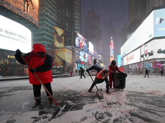 Workers clear the early snow from Times Square in New York City on Jan. 4, 2018.