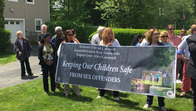 Neighbors gathered on the lawn in Congers to protest a sex offender living near a child care center, May 22, 2015.