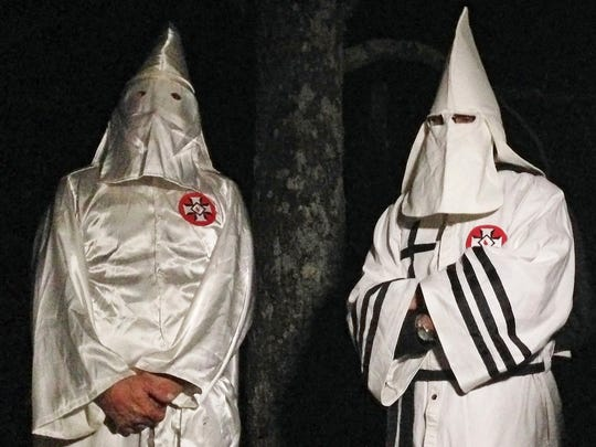 "In this Dec. 2 photo, two masked Ku Klux Klansmen stand on a muddy dirt road during an interview near Pelham. The KKK and other white extremist groups don't like being called ""white supremacists,"" a phrase that dates to the earliest days of white racist movements in the United States."