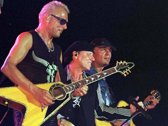 "Guitarist Rudolf Schenker(L), lead singer Klaus Meine(C) and songwriter Matthias Jabs(R) of the famed German rock group ""Scorpions"" perform at the Palace Grounds in Bangalore 09 August 2001."