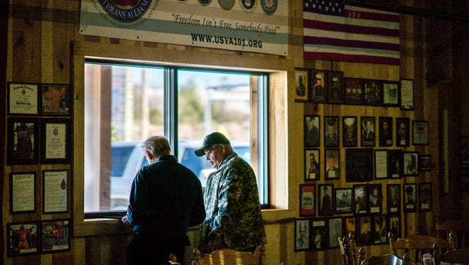 Plantation Restaurant owner Chris Lucas and U.S. Veterans Alliance President James Cripps examine photographs to be added to the Dickson, Tennessee buffet's memorial wall dedicated to Cheatham County veterans.