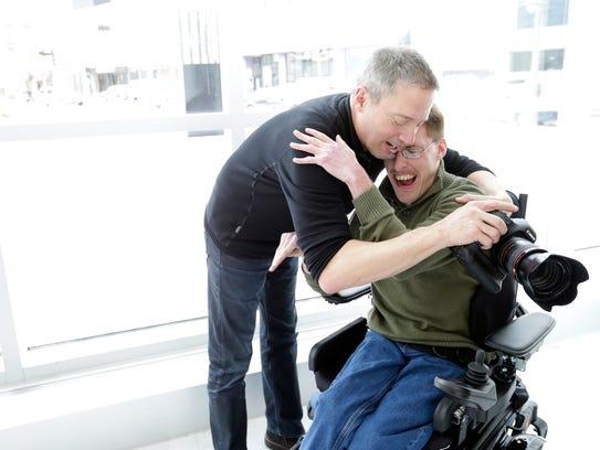 Photographer Rick Guidotti gets a hug from Bobby Fox,