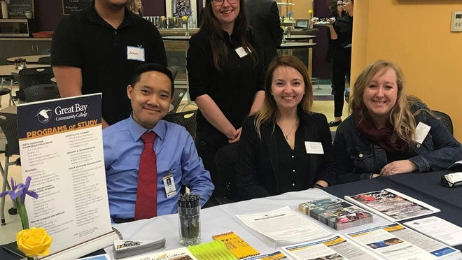 Great Bay Community College students and admissions staff welcome attendees to its career expo with local industry experts in April 2019.