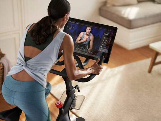 A woman exercising on a Peloton bike.