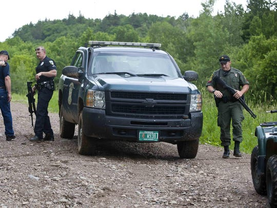 A Milton police officer and a Vermont game warden get out of a truck holding long guns at the bottom of a road leading to a deer camp where two people were injured off Clay Ridge Road in Milton on June 18, 2014.