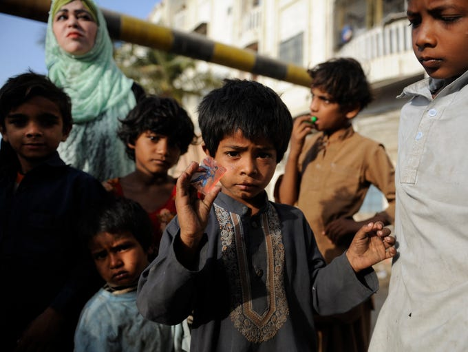 A young man in Karachi, Pakistan, holds on to a tiny