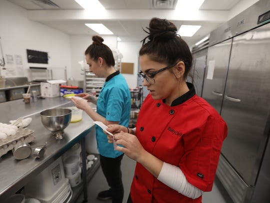 Ryan Piccini, foreground, and Jodi Rivera, consult the handwritten recipes as they work on baking several variety of cookies for the April 10 opening.