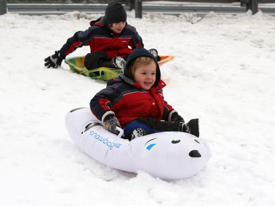 Children sled on the snow-covered hill behind East Brunswick High School in 2012.