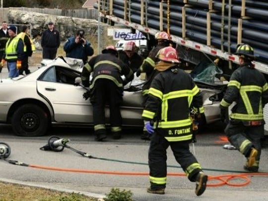 Dean Fontaine, foreground, and other firefighters respond to a car crash.