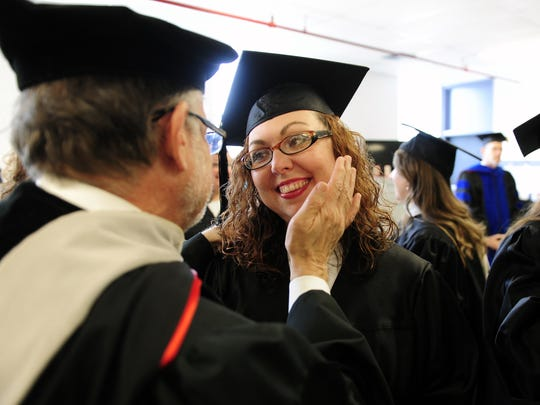 Lipscomb University professor Paul Prill congratulates Tennessee Prison for Women inmate Tabitha Slack for earning her associate's degree in this file photo from 2013.