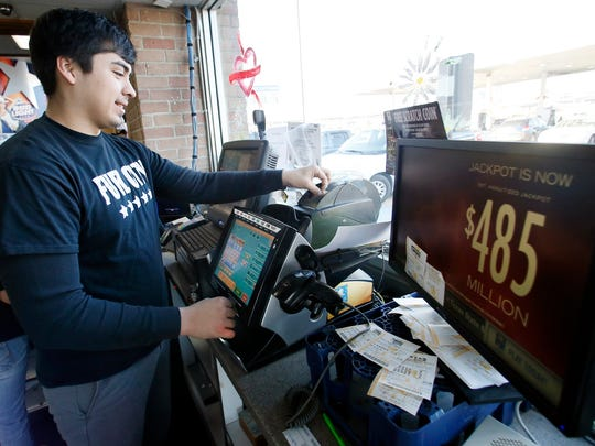 Cashier Ezequiel Villareal prints out a Powerball ticket for a customer at Fuel City Tuesday in Dallas.