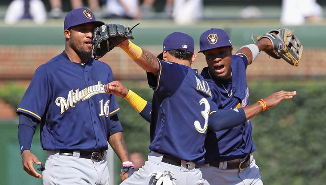Domingo Santana (from left), Orlando Arcia and Keon Broxton celebrate after the Brewers pounded the Cubs, 11-2, on Thursday at Wrigley Field.
