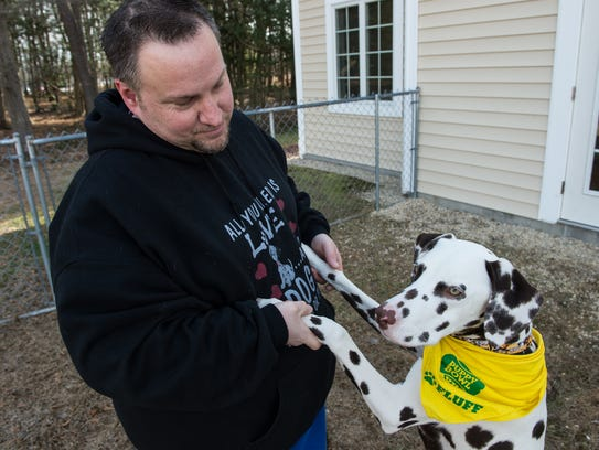 Randy Creasy holds his dog Chance at the Animal Wellness