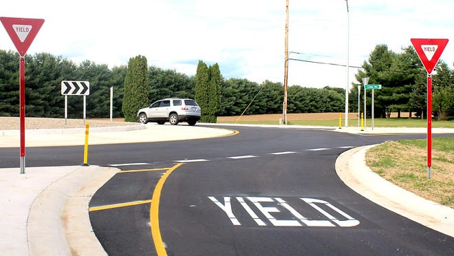 A vehicle travels around the new roundabout at the intersection of Colon and Farrand roads.