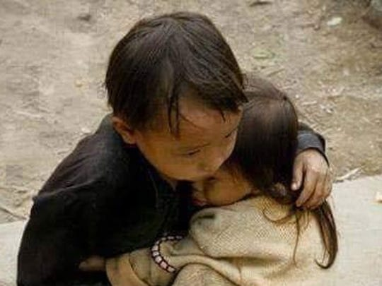 Two young children in Nepal find comfort with each other.
