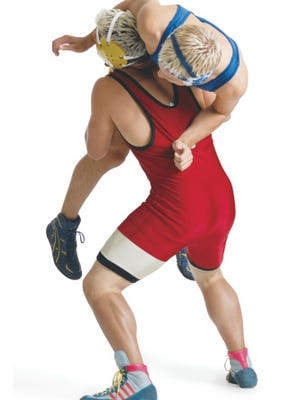 Two male wrestlers from opposing teams fight as the one in red lifts up the one in blue.