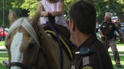 In this 2013 file photo, members of the Ottawa County Sheriff's Office Mounted Unit let children ride their horses at the annual Holland National Night Out in Kollen Park.