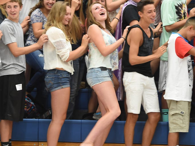 Poudre High School freshman, Elsa Berkner, 14, middle, playfully lifts her leg as friend and fellow classmate, scratches her back, at an assembly in the school's gym, during the first day of school at Monday Aug. 18, 2014.