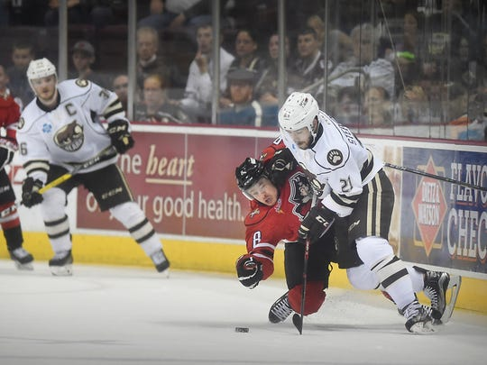 Hershey Bear Chandler Stephenson (21) and Portland Pirate Brent Regner (8) collide against the glass Sunday, May 1, 2016, at the Giant Center in Hershey.