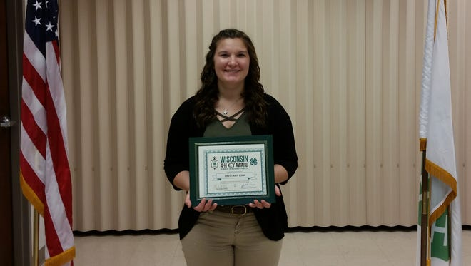 Brittany Fink holds her Wisconsin 4-H Key Award certificate. Fink, the daughter of John and Vicky Fink,  is a member of the Lomira Clover Leaves 4-H Club.