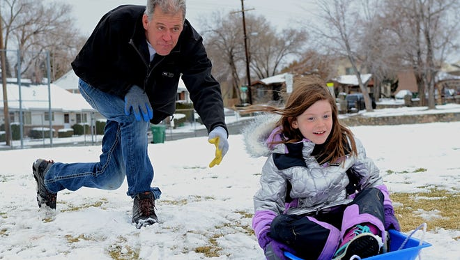 Mark Hain, 55, pushes his 7-year-old daughter, Gracie, down a snow hill at Plumas Park on March 2, 2018 in Reno.