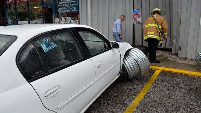 A firefighter and Gill-Roy's employee inspect the wall of Gill-Roy's hardware store after a car drove into the wall Friday in Port Huron.