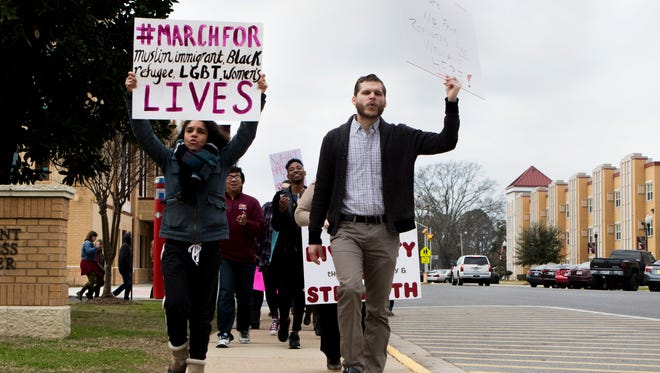 Vanelis Rivera, an English instructor, and Chris Wade, a recent graduate, lead a march through ULM's campus on Saturday, February 4, 2017. Approximately 50 students, faculty, staff, local faith leaders and community members attended the demonstration to voice their opposition to President Donald Trump's executive order banning immigrants and refugees from 7 majority Muslim countries from entering the United States.