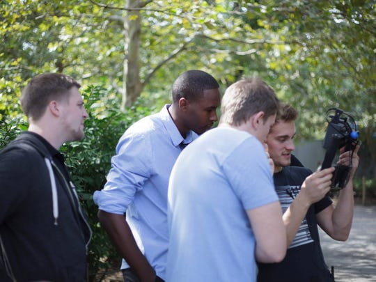 """The crew of """"The Cager"""" look at a playback of a scene during filming in September 2014. Second from left is lead actor Delvon Roe, and next to him is director Keenan Wetzel. Both have played basketball at MSU."""